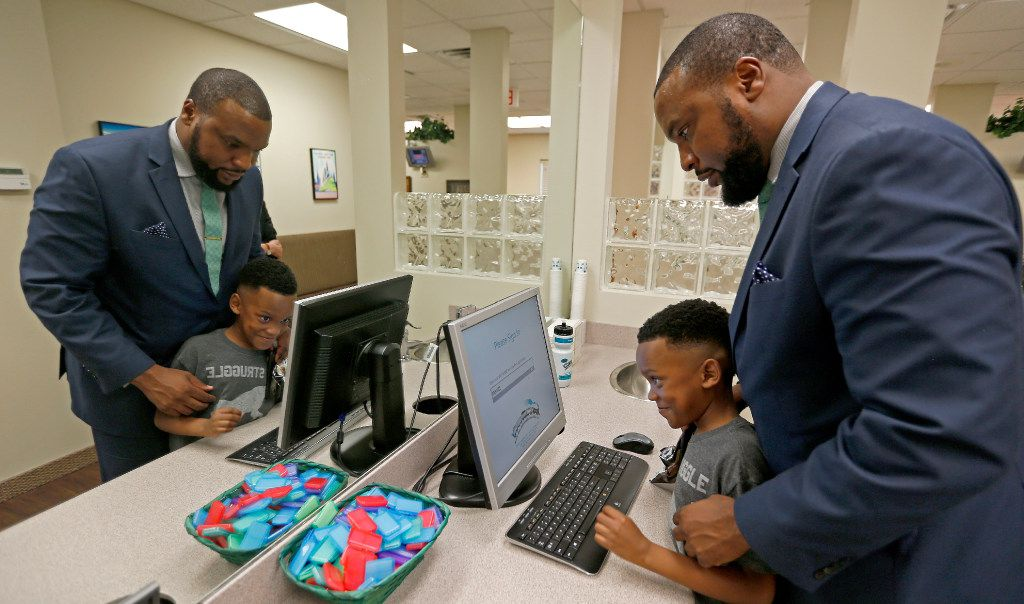 Attorney Lee Merritt (right) helps his 7-year-old son Stacy Merritt, Jr., check in on the computer at the North Texas Orthodontic Associates' office in Allen.