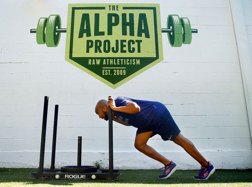 Donovan Lewis pushes a weighted sled across the turf during his workout behind the Alpha Project gym in Dallas,
