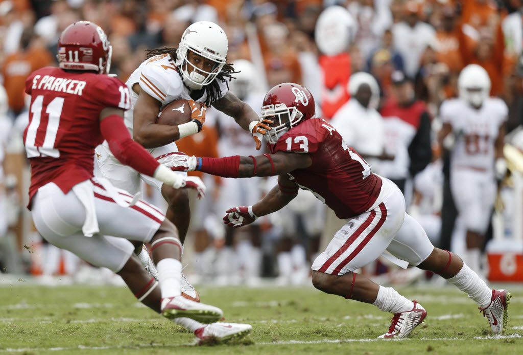 Texas Longhorns wide receiver Marcus Johnson (7) attempts to break a tackle by Oklahoma Sooners safety Ahmad Thomas (13) while moving with the ball in the second quarter during an NCAA college football game between the Texas Longhorns and the Oklahoma Sooners at the Cotton Bowl in Dallas Saturday October 11, 2014. Oklahoma Sooners beat the Texas Longhorns 31-26. (Andy Jacobsohn/The Dallas Morning News)