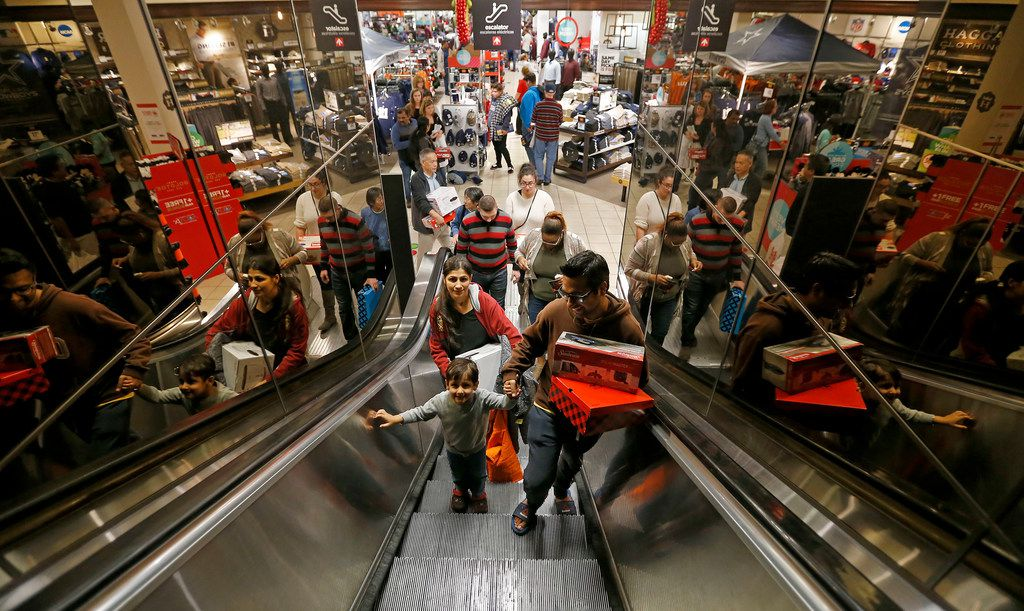 Shopper Puneet Dua (right), his wife Richa (left) and 3-year-old son Mansh ride an escalator while shopping at the J. C. Penney store inside Collin Creek Mall in Plano on Nov. 23, 2017.