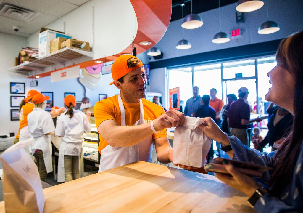 Rise Biscuits Donuts employee Brice Bode serves a customer during a grand opening event on Thursday, March 30, 2017 at Rise Biscuits Donuts in Allen, Texas. (Ashley Landis/The Dallas Morning News)