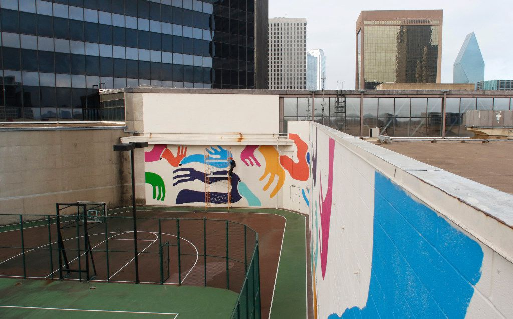 Muralist Kyle Steed puts the finishing touches on his mural at the Plaza of the Americas building in downtown Dallas7. (David Woo/The Dallas Morning News)