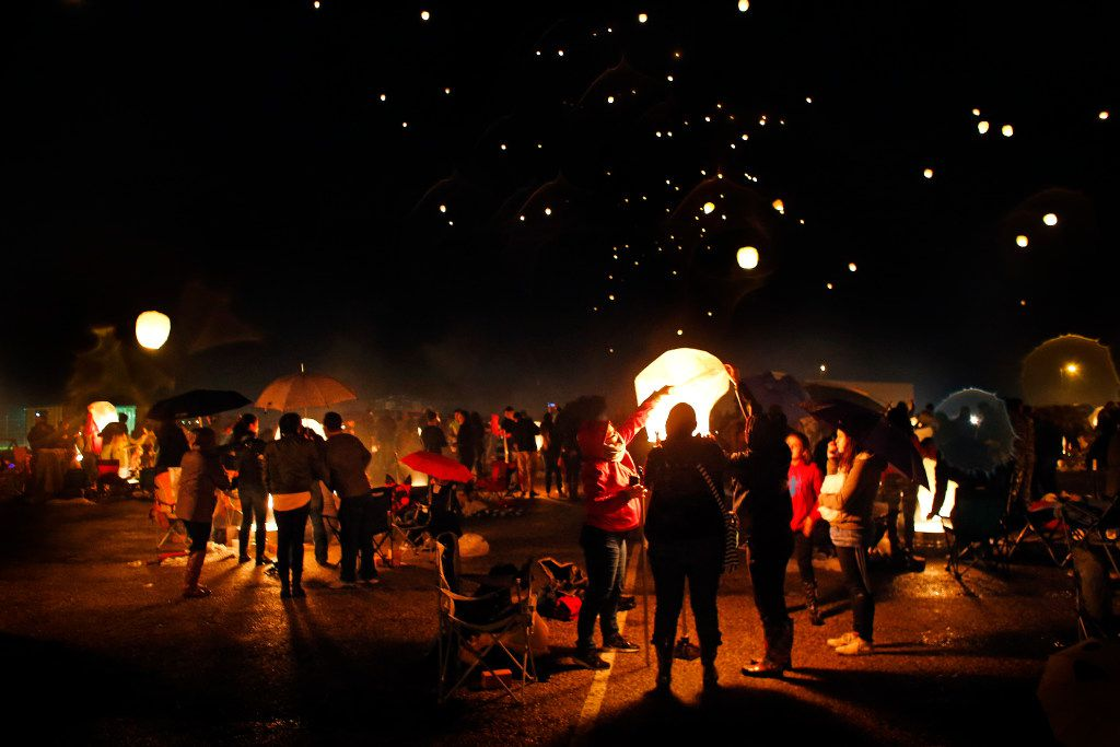 People light paper lanterns and release them into the night sky during the Lantern Festival at Texas Motorplex in Ennis, Texas, Saturday, March 4, 2017. (Tom Fox/The Dallas Morning News)