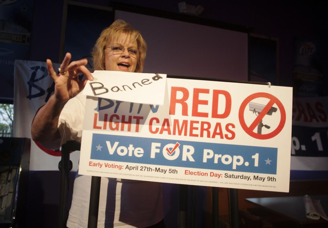 "Arlington petition drive leader Kelly Canon taped an update to a ""Ban Red Light Cameras"" sign to celebrate success on election night May 9. She's eager to help other activists looking at launching petition drives in their cities: ""We're going to be sharing how we did it with whoever wants to know."""