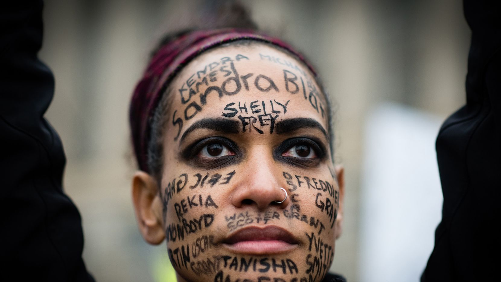 Aisha Bain, 38, of Baltimore has the names of African-Americans who died from violence written on her face. She was marching with the organization Move to End Violence.