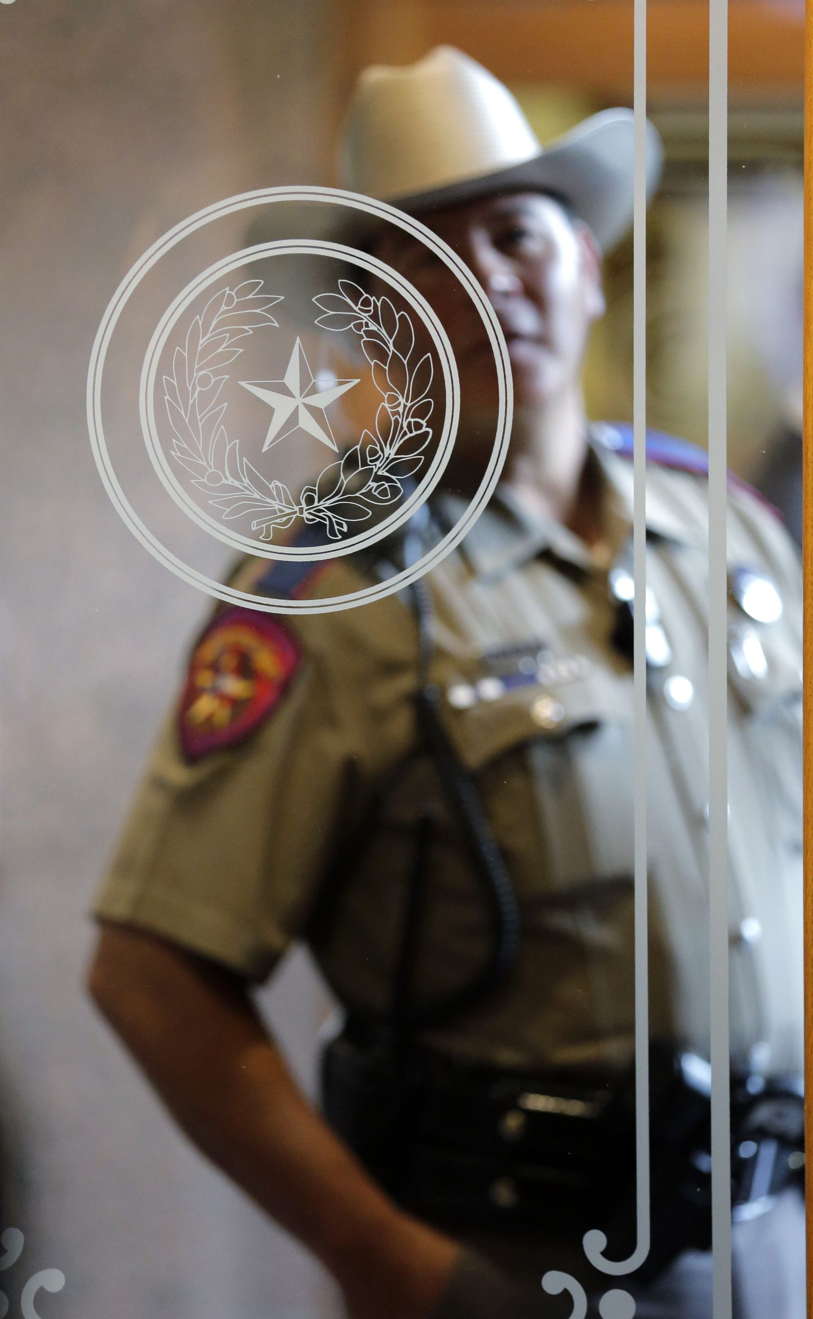 A Texas state trooper stands outside of a hearing where lawmakers discuss whether to legalize concealed handguns on college campuses and open carry everywhere else last month.