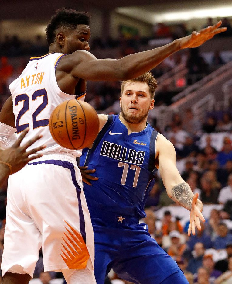 Dallas Mavericks guard Luka Doncic (77) dishes around Phoenix Suns center Deandre Ayton (22) during the first half of an NBA basketball game, Wednesday, Oct. 17, 2018, in Phoenix. (AP Photo/Matt York)