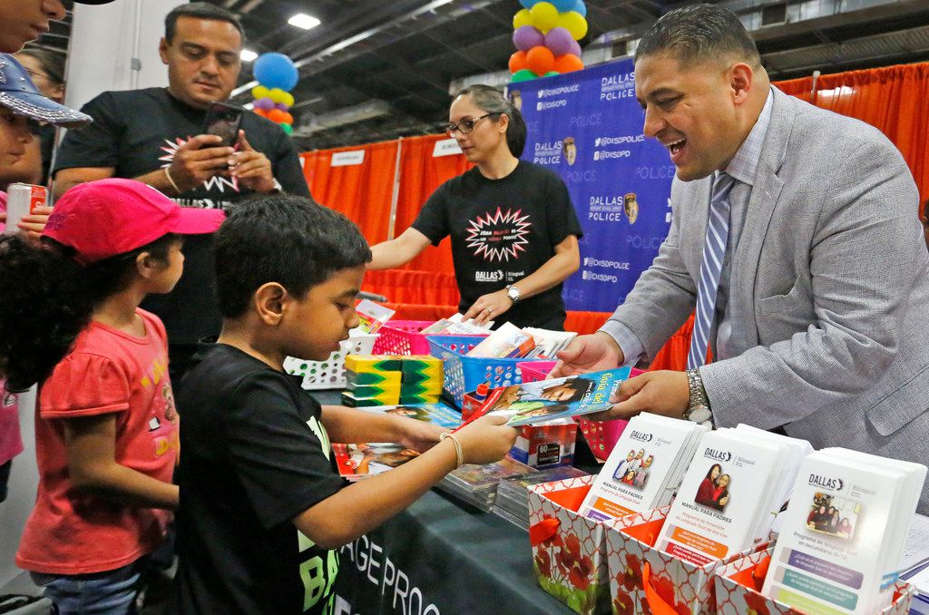 Dallas school board member Jaime Resendez hands out items to parents and students at the Bilingual ESL/Dual Language Programs  booth at the Dallas Mayor's Back to School Fair held at the Centennial Building at Fair Park on Aug. 3, 2018.