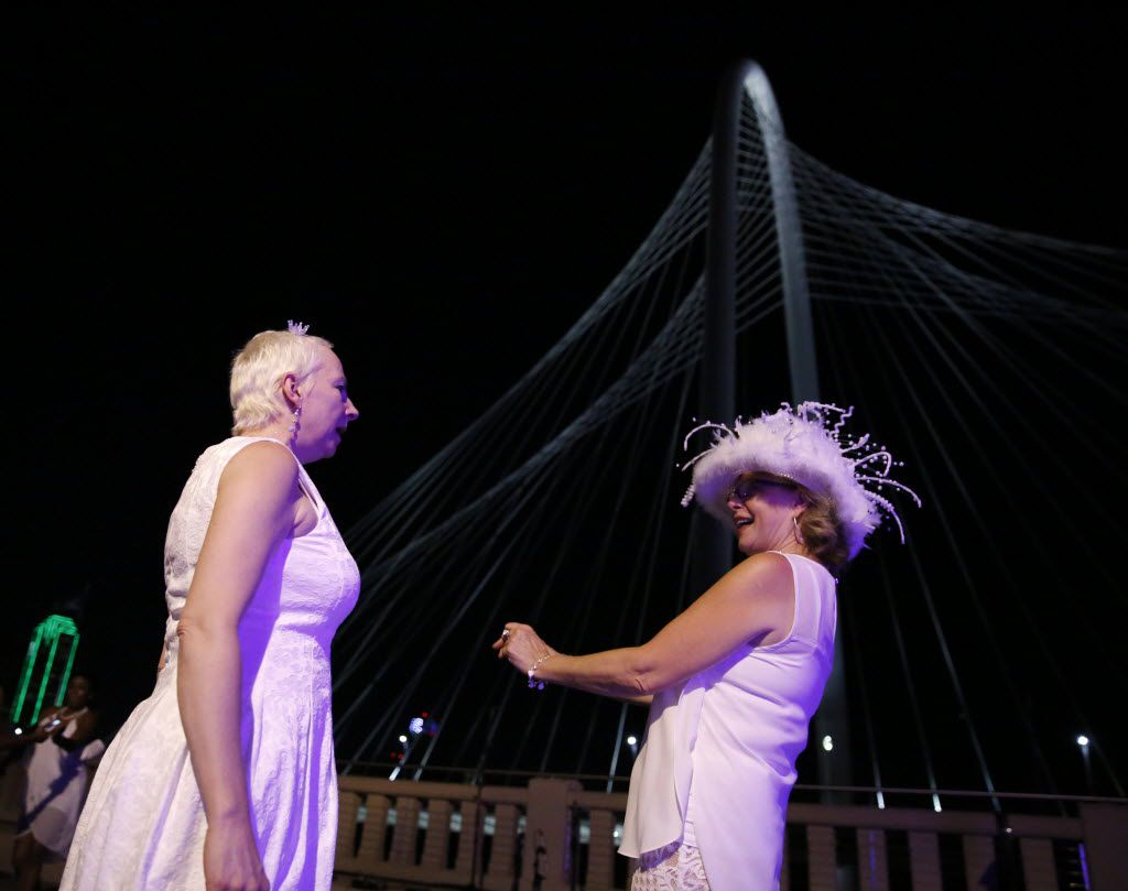 Nancy Silva (left) dances with Elizabeth Taylor during the inaugural Diner en Blanc Dallas on the Continental Avenue Bridge in Dallas on Sept. 17, 2015. Exactly 1,678 people attended the event, which requires dinner guests to dress all in white and bring their own chairs and centerpieces. As per tradition, the location was kept private leading up to the event.