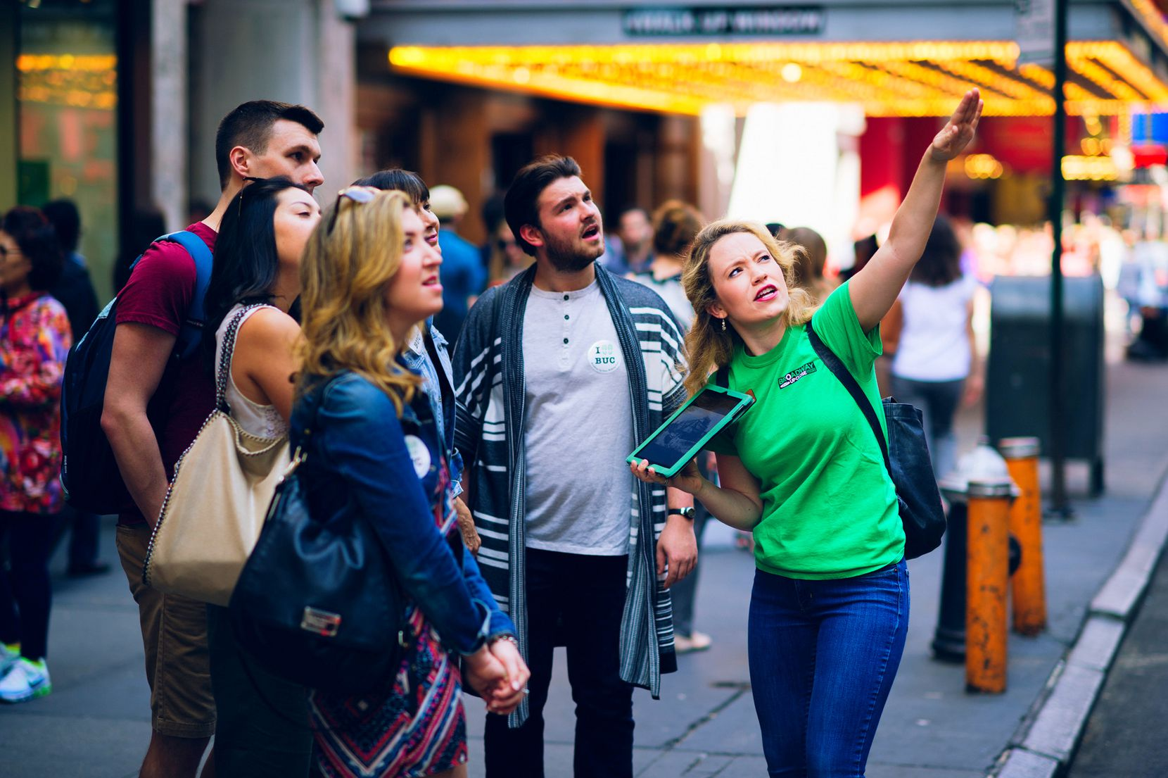 The green-clad guides for the Broadway Up Close tour company carry an iPad filled with period photos and video clips to bring theater history to life.