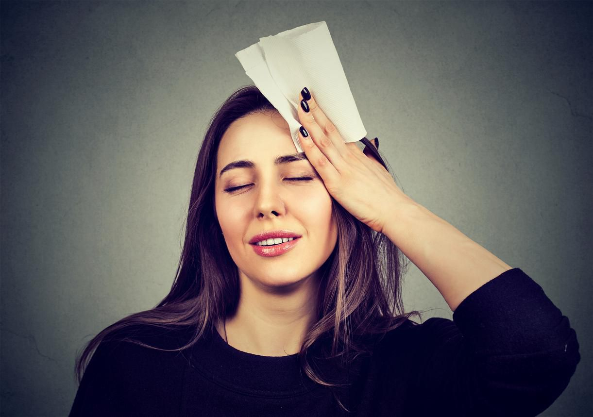 young woman wipes sweat from her forehead with a handkerchief(iStock)