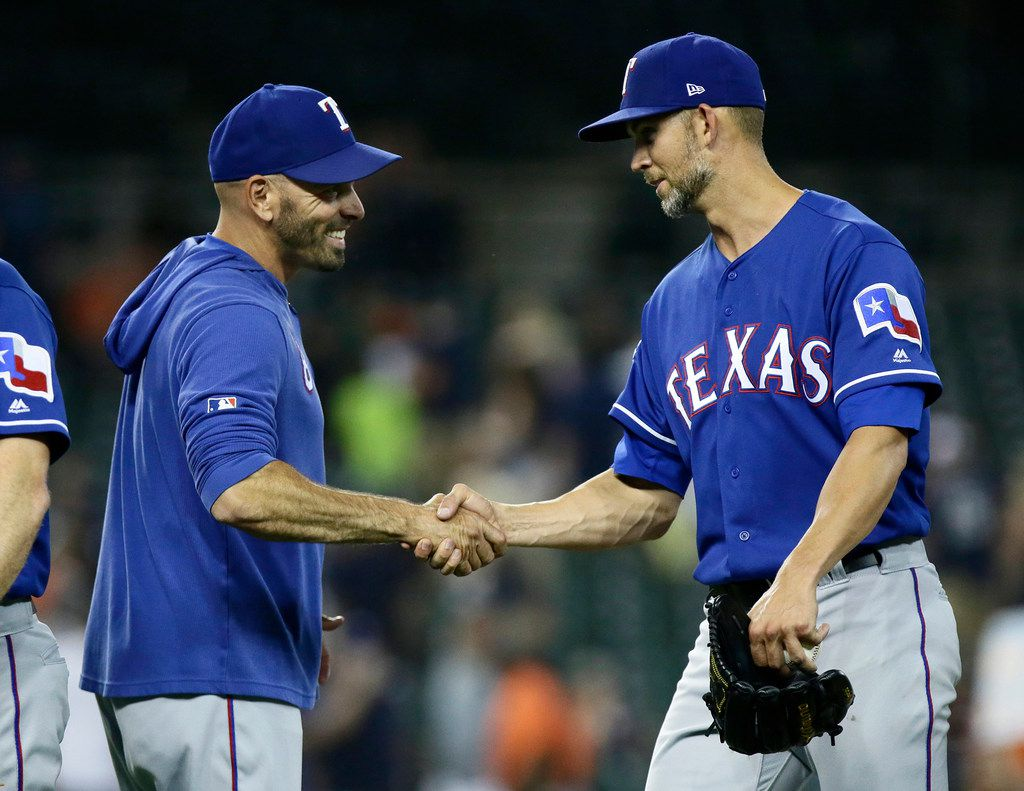 Manager Chris Woodward of the Texas Rangers congratulates starting pitcher Mike Minor, right, after pitching a complete-game 4-1 victory against the Detroit Tigers at Comerica Park in Detroit on Wednesday, June 26, 2019. (Duane Burleson/Getty Images/TNS) **FOR USE WITH THIS STORY ONLY**