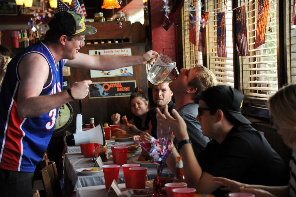Gavin Mulloy hydrates contestant Ryan Berry at the 7th annual Brass Knuckles Corn Dog Beatdown at The Libertine Bar on July 4, 2015.