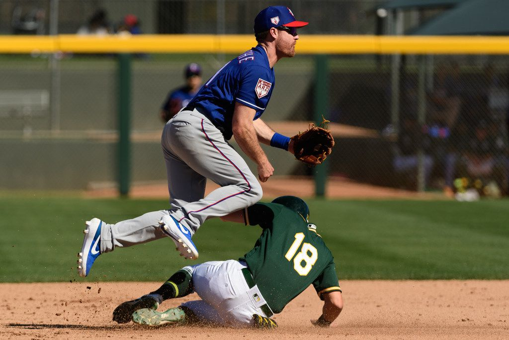 MESA, ARIZONA - MARCH 05: Logan Forsythe #41 of the Texas Rangers turns the double play over Chad Pinder #18 of the Oakland Athletics during the spring training game at HoHoKam Stadium on March 05, 2019 in Mesa, Arizona. (Photo by Jennifer Stewart/Getty Images)