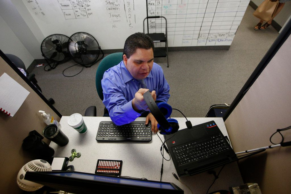 Al Rodriguez grabs his headphones at his desk in the call center at Bold Sales Solutions, a subsidiary of Dallas Lighthouse for the Blind in Dallas on June 30, 2017.  (Nathan Hunsinger/The Dallas Morning News)