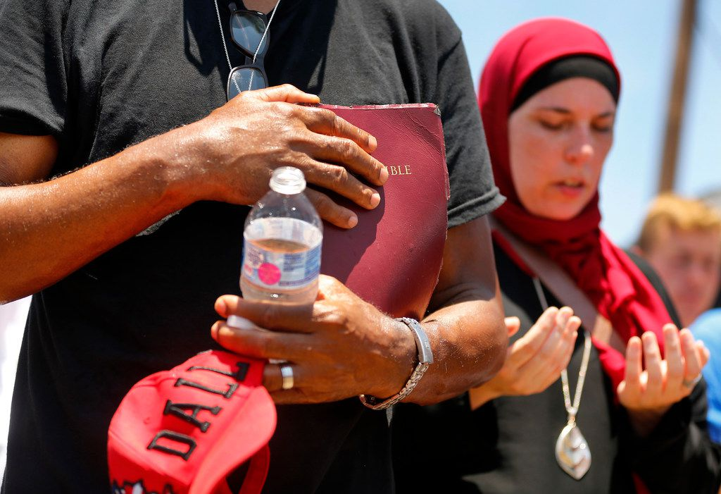 The Rev. Peter Johnson grasps his bible and he an other Dallas religious leaders pray outside the US Border Patrol Processing Center in McAllen, Texas, Saturday, June 23, 2018. The group was there to protest the border policies for immigrants crossing into the United States from Mexico.