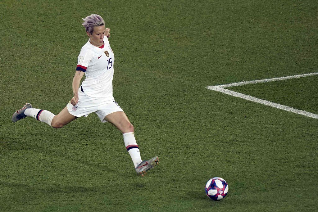 """(FILES) In this file photo taken on June 28, 2019, USA forward Megan Rapinoe scores a goal during the France 2019 Women's World Cup quarter-final football match between France and USA, on June 28, 2019, at the Parc des Princes stadium in Paris. - Megan Rapinoe, captain of the US women's football squad, has accepted an invitation from US Representative Alexandria Ocasio-Cortez to visit the House of Representatives, just days after bluntly saying she would refuse a similar offer from US President Donald Trump. """"It may not be the White House, but we'd be happy to welcome @mPinoe & the entire #USWMNT for a tour of the House of Representatives anytime they'd like,""""Ocasio-Cortez tweeted on June 28, 2019. """"Consider it done,"""" Rapinoe  quickly replied (Photo by Kenzo TRIBOUILLARD / AFP)KENZO TRIBOUILLARD/AFP/Getty Images"""