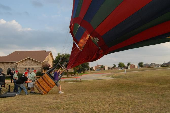 Pat Cannon hits the burners to add hot air to his balloon, lifting the balloon to a vertical position as members of the Lion's Club help keep the ballon straight and settled on the ground.