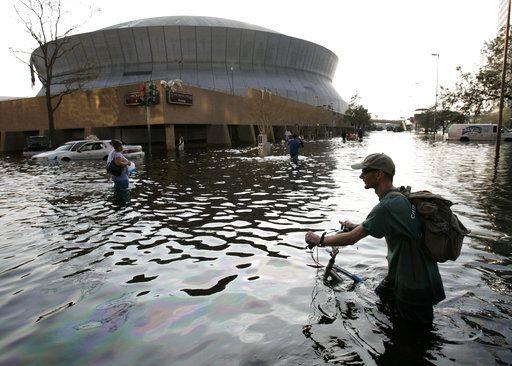 En una foto de archivo del 31 de agosto de 2005, se ve a un hombre empujando su bicicleta a través de unas aguas cerca del Superdome de Nueva Orleáns, después de que el Huracán Katrina dejó a gran parte de la ciudad bajo agua. Algunos residentes de Nueva Orleáns tienen recuerdos tristes de ese evento ahora que la tormenta Harvey amenaza a esa ciudad, exactamente 12 años después de que ocurrió Katrina. Foto AP.