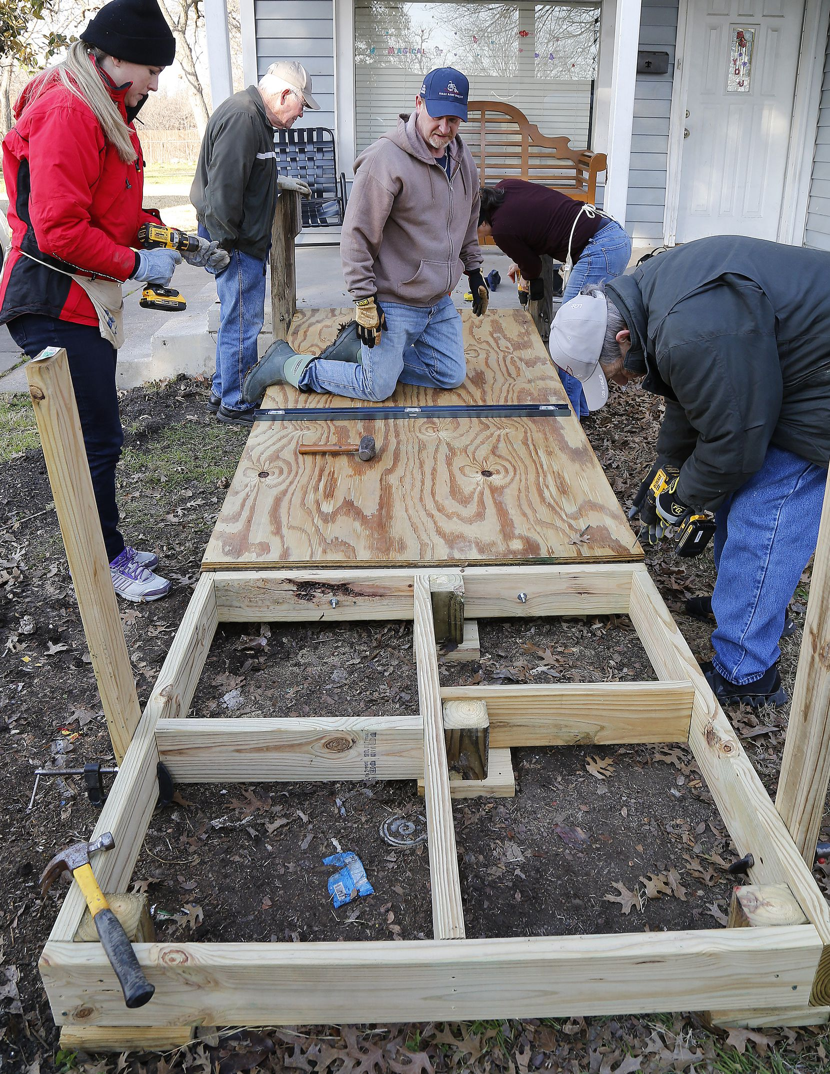 Project manager Kirk Saxon (center) of Melissa, Texas surveys the situation from his knees as The Kiwanis Club of McKinney builds a wheelchair ramp at the home of Rachel Armijo, in McKinney on Saturday morning, January 26, 2019.
