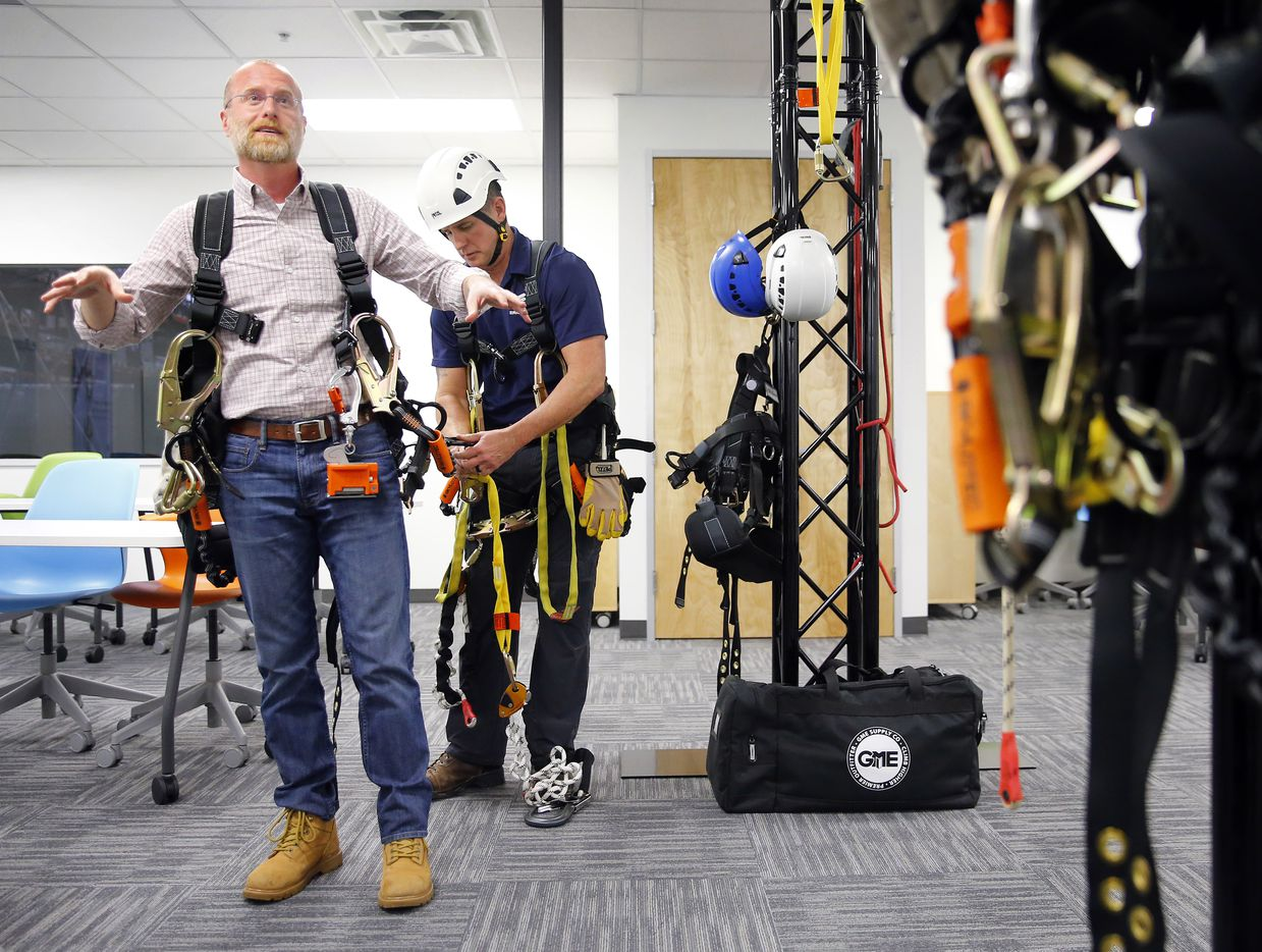 Federal Communications Commission commissioner Brendan Carr (left) is put in a harness by Rick Flynt before performing a controlled descent while on tour of Swedish telecom company Ericsson's tower training facility in Lewisville, Texas, Monday, February 4, 2019. Earlier he was part of a ribbon cutting on the new Center of Excellence.