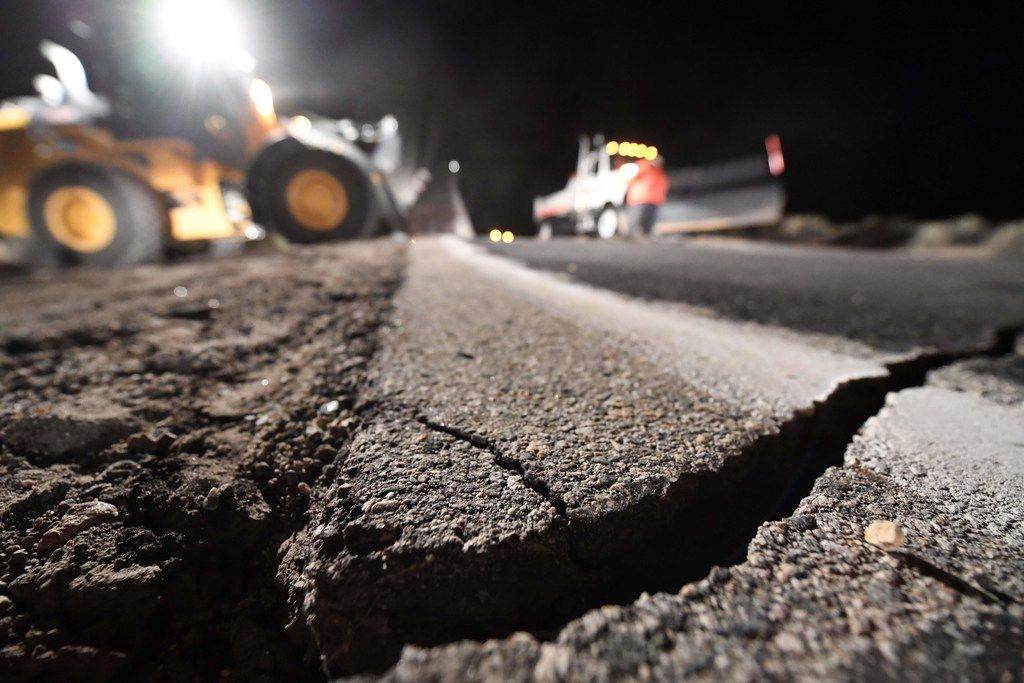 Highway workers repair a hole that opened in the road as a result of the July 5, 2019 earthquake, in Ridgecrest, Calif., about 150 miles north of Los Angeles, early in the morning on July 6, 2019.
