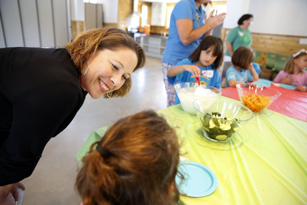 Girl Scouts of Northeast Texas CEO Jennifer Bartkowski (left) listens to young girls explain their day during day camp at the Girl Scouts STEM Center of Excellence at Camp Whispering Cedars in Dallas.