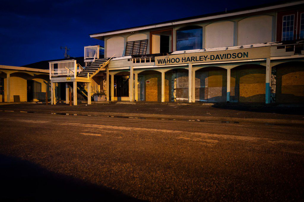 The setting sun casts a glow on business across the street from Shorty's Place, including Wahoo Harley-Davidson, that remain vacant nearly a year after Hurricane Harvey devastated the Texas Gulf Coast city of Port Aransas.