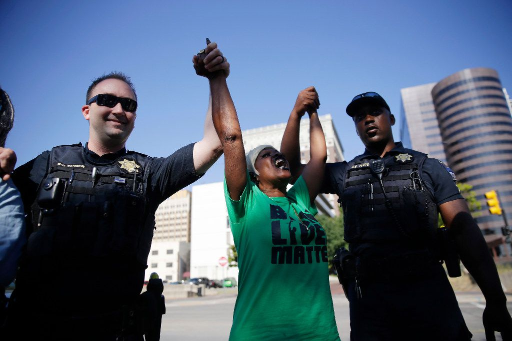 Angie Pitts of Tulsa holds hands with police officers while protesting the death of Terence Crutcher, who was shot by police.