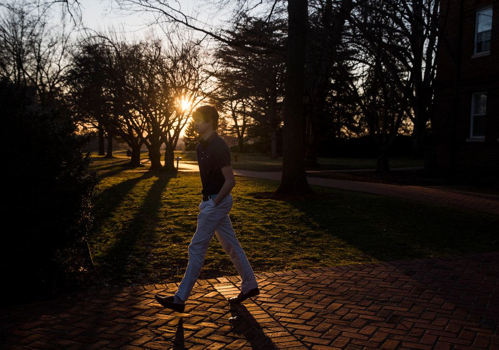 As the sun descends, a student make his way to the dining hall for dinner at Woodberry Forest School.