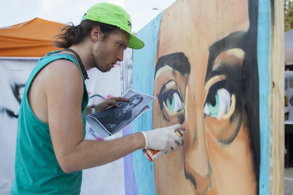 Daniel Black spray paints a portrait near the Audacity Brew House main stage on the final day of Oaktopia on Sunday, September 27, 2015.