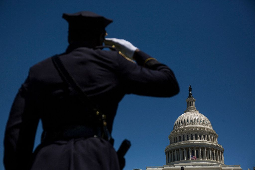A law enforcement officer salutes as names are read during a roll call of fallen officers during the 36th Annual National Peace Officers' Memorial Service on the West Lawn of The U.S. Capitol Building Monday, May 15, 2017 in Washington, D.C.  The service, which takes place every year on May 15, honored federal, state, and local officers killed or disabled in the line of duty.  (Zach Gibson/Special Contributor)
