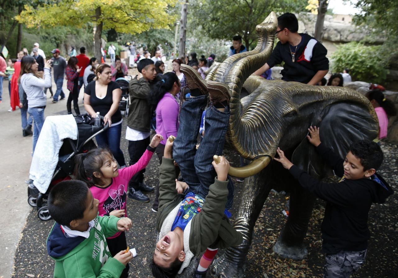 Niños juegan en una figura de metal del elefante, en el zoológico de Dallas, el previo Día del Dollar, en noviembre. (DMN/ROSE BACA)