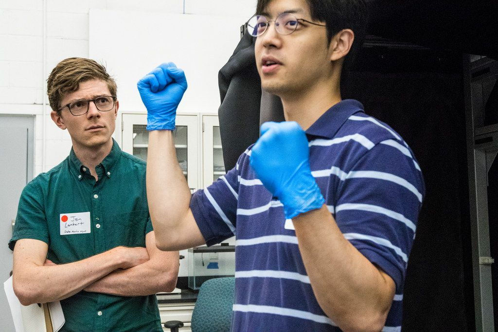 Jon Lambert, of The Dallas Morning News, left, listens to Southern Methodist University graduate student Jung Soo Lee speak during Science in the City at SMU in Dallas in 2018.
