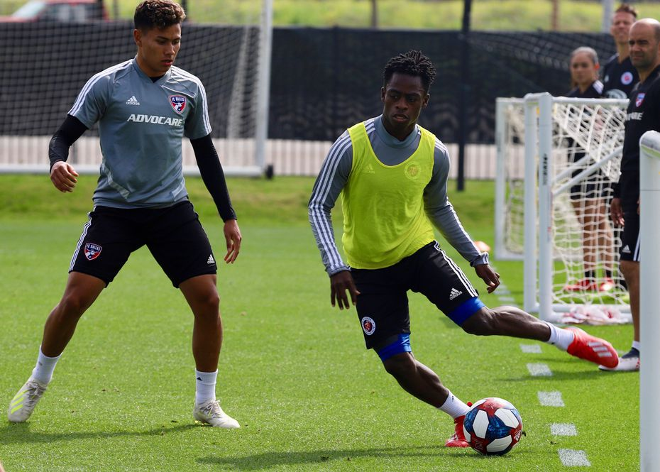 Ronaldo Damus winds up for a pass while marked by Edwin Cerrillo in a combined FC Dallas and North Texas SC training session. (4-23-19)