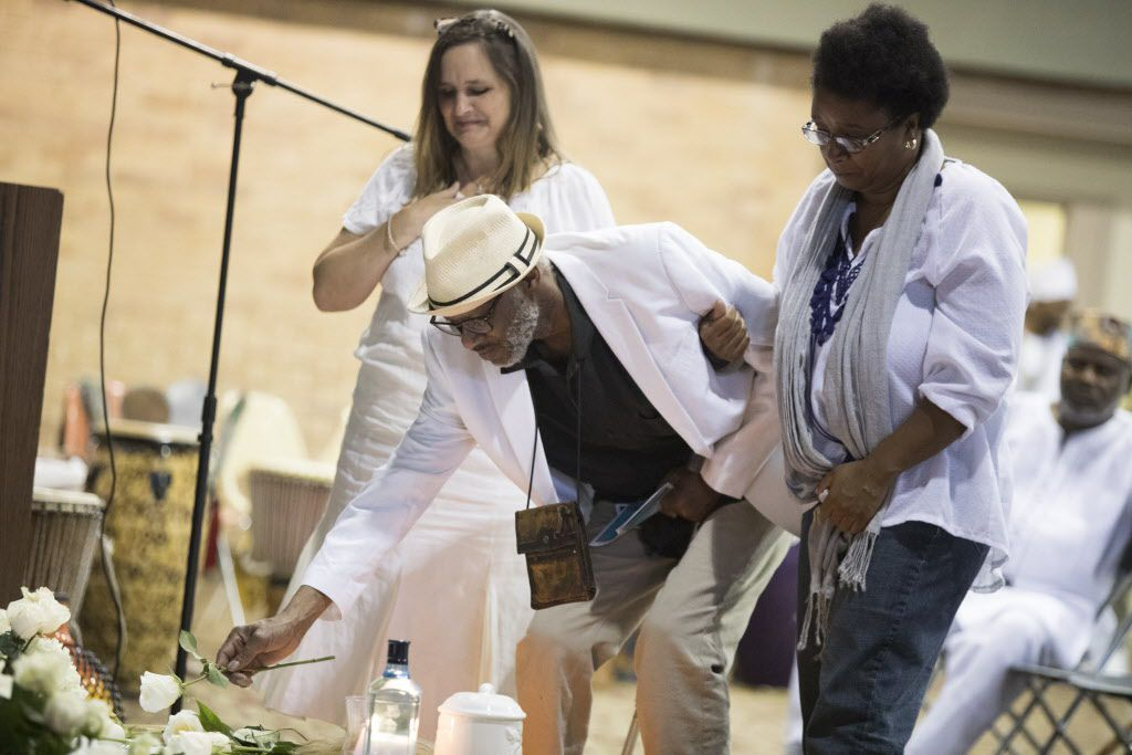 Charles Hillman, center, places a rose on an alter during a memorial service for Arthur Riggins, also affectionately known as Baba and Chief Ifayomi by the community, on May 19, 2017, at the Frederick Douglass Community Center in Dallas, Texas. Hillman worked with Riggins for over 30 years on the many festivals and outreach effects throughout the community. (Andrew Buckley/Special Contributor)