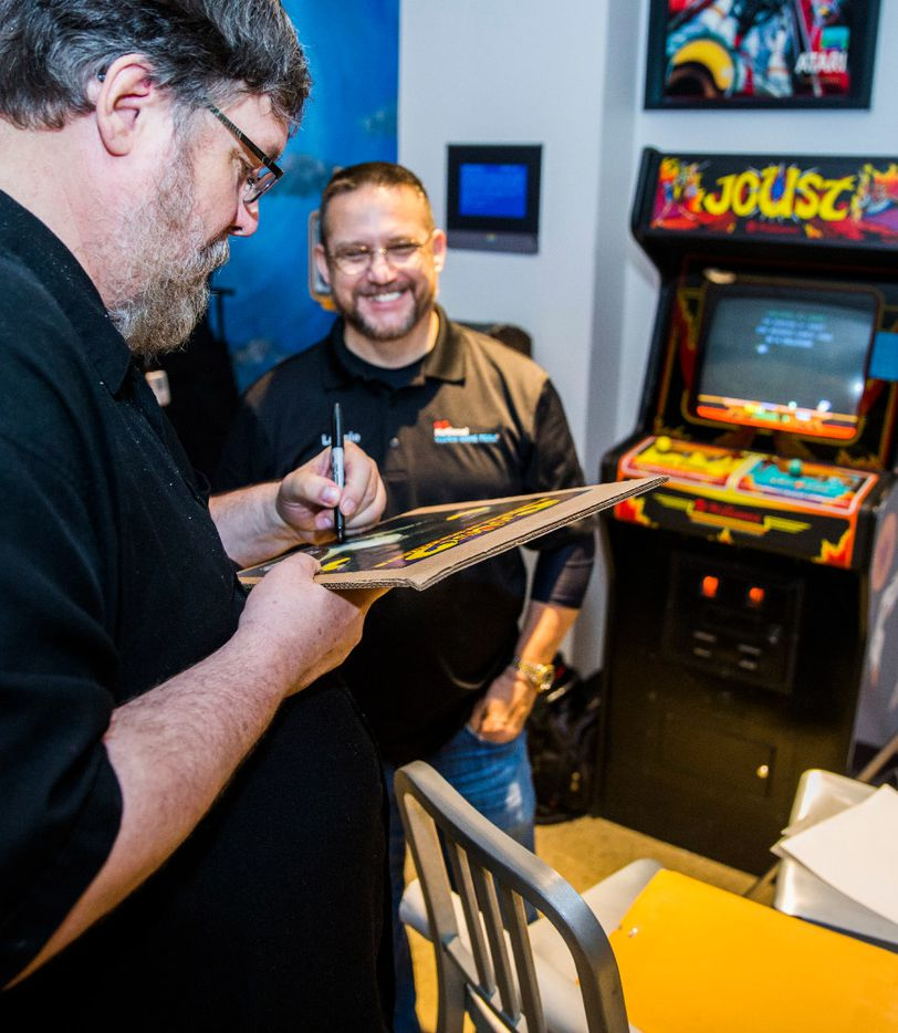 Arcade game Joust creator John Newcomer, left, signs a poster for Lonnie McDonald, right, who scored on a high score on the video game Joust on Wednesday, March 22, 2017 at The National Videogame Museum in Frisco, Texas. McDonald, a self-proclaimed Joust master, is touring the country to post a score of 9,999,999 on every Joust arcade machine known to exist. He did it for the 150th time at The NVM, with a score of 10,214,800, which took him about six hours. (Ashley Landis/The Dallas Morning News)