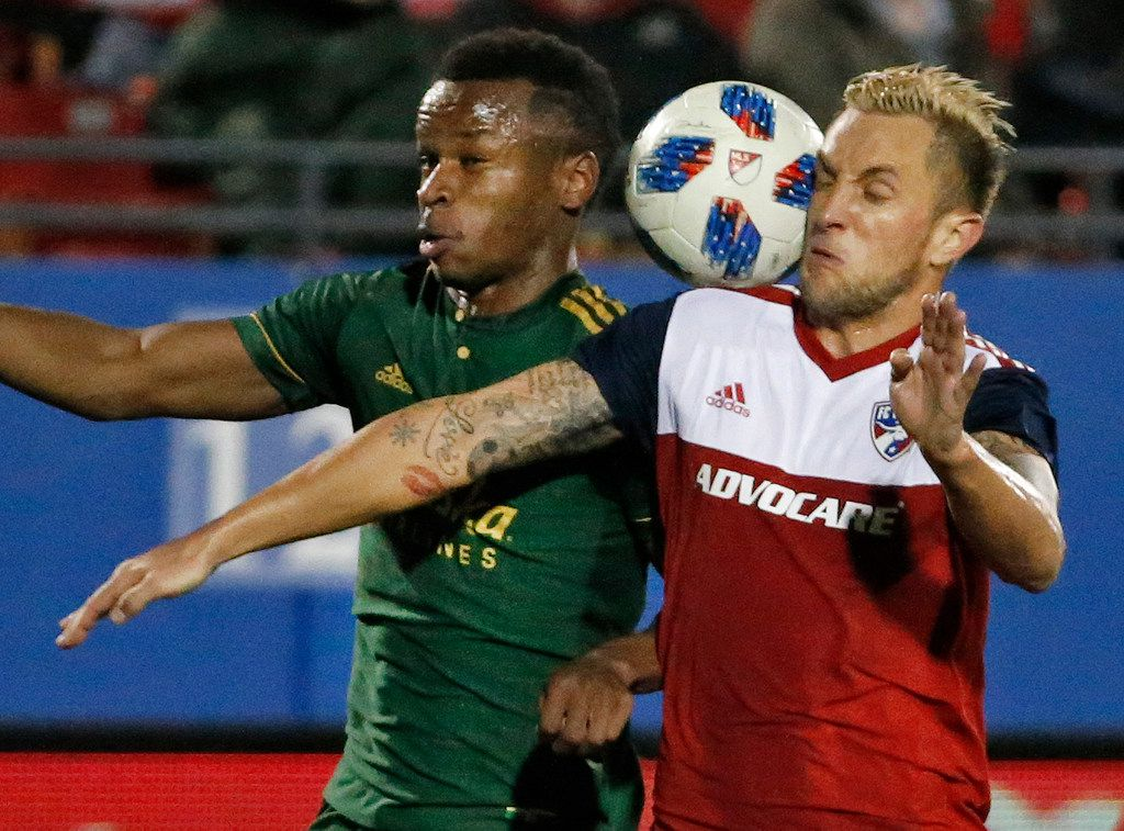 Portland Timbers forward Jeremy Ebobisse (17) and FC Dallas defender Reto Ziegler (3) try to control the ball in the second half during the FC Dallas vs. the Portland Timbers playoff soccer game at Toyota Stadium in Frisco, Texas on Wednesday, October 31, 2018. (Louis DeLuca/The Dallas Morning News)