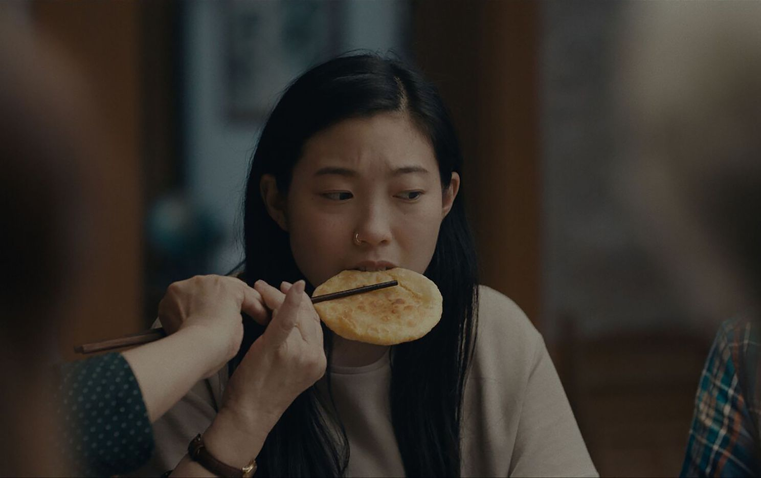 Billi (Awkwafina) accepts food from her grandmother's chopsticks in The Farewell.