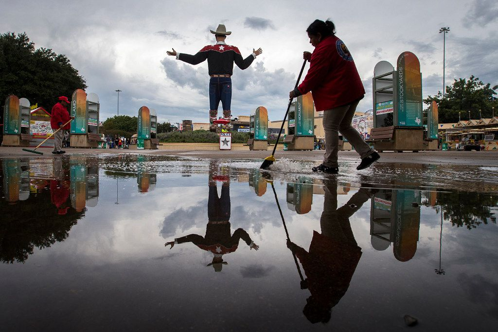 Fair employees sweep water toward drains as they work to clear standing water after a morning rain during the State Fair of Texas at Fair Park. (Smiley N. Pool/The Dallas Morning News)