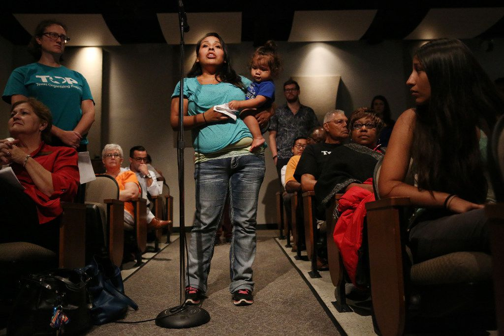 Mandy Lee-Vielma, who has three children in DISD, holds onto her fourth child, Grayson Padilla, 1, while speaking in support of a 13-cent tax ratification election during a public hearing and board meeting of the Dallas Independent School District at the Dallas ISD headquarters on Aug. 18.