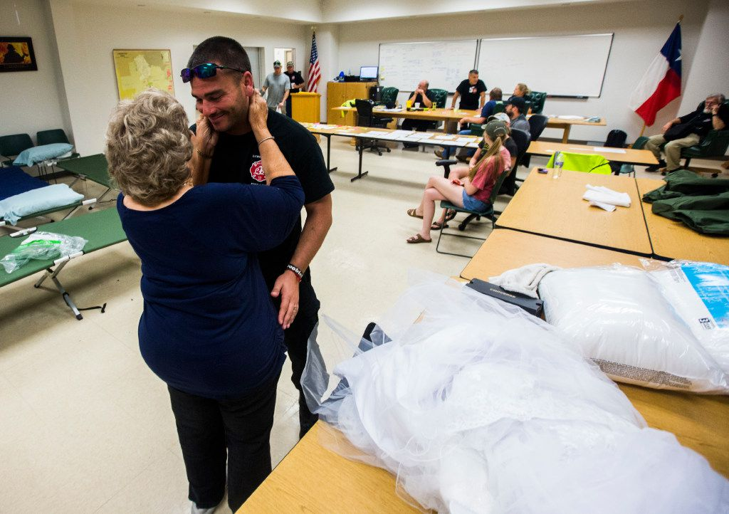 Joyce Brown, left, office manager of the Lumberton Central Fire Station, talks to Firefighter Kyle Parry, who retrieved the wedding dress of his fiancé, Stephanie Hoekstra, not pictured, of Chatham-Kent, Ontario, Canada, from his home, which is flooded as a result of Tropical Storm Harvey on Thursday, August 31, 2017 in Lumberton, Texas. Parry and Hoekstra are supposed to be married on September 10 in Galveston, TX. Parry's home is destroyed, but he was able to retrieve the dress. (Ashley Landis/The Dallas Morning News)