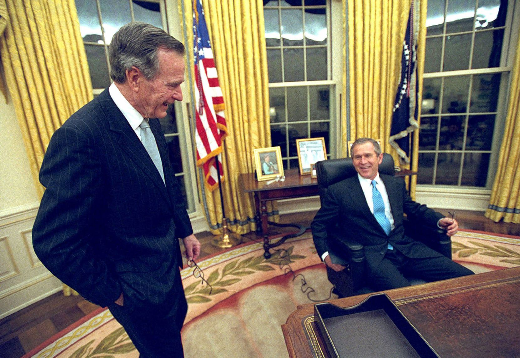 2001: President George W. Bush talks to his father, former President George H.W. Bush, as he sits at his desk in the Oval Office for the first time after the younger Bush's inauguration.