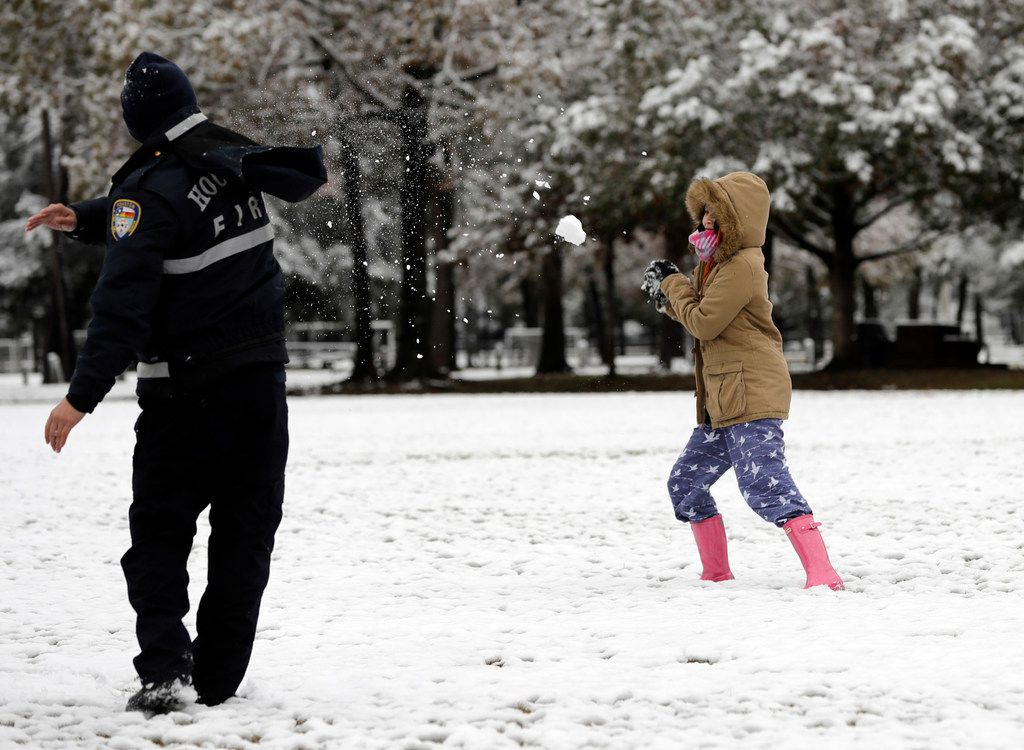 Houston Fire Department firefighter Phuoc Ngo, left, throws a snowball toward his wife Christine Co while playing in the snow Friday, Dec. 8, 2017, in Spring, Texas, north of Houston. Rare snowfall in many parts of southern Texas has knocked out power to thousands, caused numerous accidents along slick roadways and closed schools. The weather band brought snow to San Antonio, Corpus Christi, Houston and elsewhere.