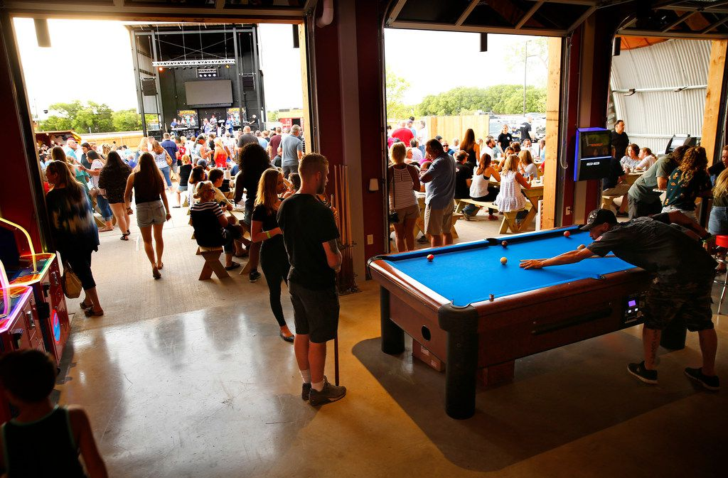 The garage doors lead patrons from the bar to the outdoor music venue during opening night at ChopShop Live in Roanoke, Texas, Friday, July 6, 2018. (Tom Fox/The Dallas Morning News)
