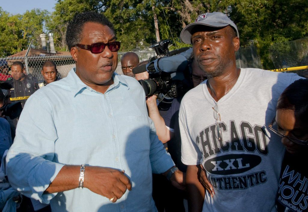 Dallas city councilman Dwaine Caraway, left, walks with James White, father of James Harper, the suspect killed in an officer involved shooting at Dixon Avenue and Bourquin Street in southeast Dallas on July 24, 2012. (Jeff Lautenberger/The Dallas Morning News)  -- police shooting of James Harper in the Dixon Circle community