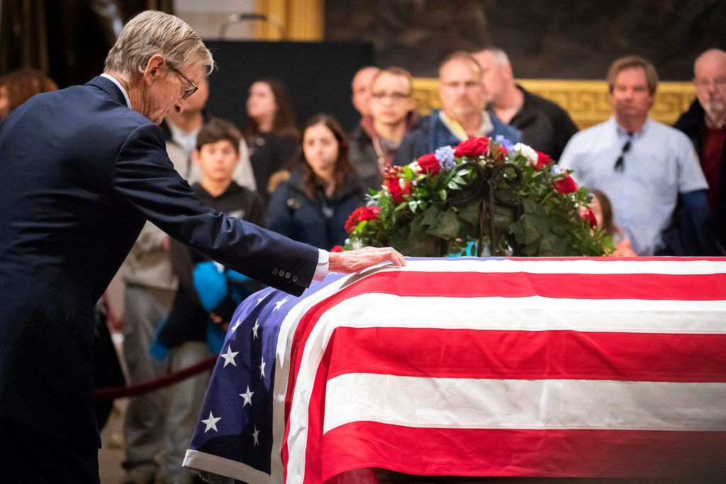 Jonathan J. Bush, the brother of the former President, visits the flag-draped casket of President George H.W. Bush as he lies in the Rotunda of the U.S. Capitol on Tuesday, Dec. 4, 2018, in Washington.
