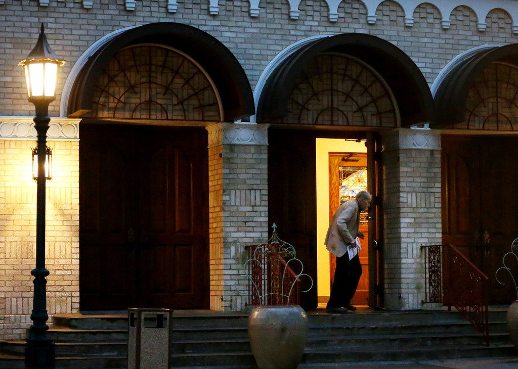 """A parishioner leaves St. John after Mass on Friday. One parishioner called it """"a sad day for the church."""""""