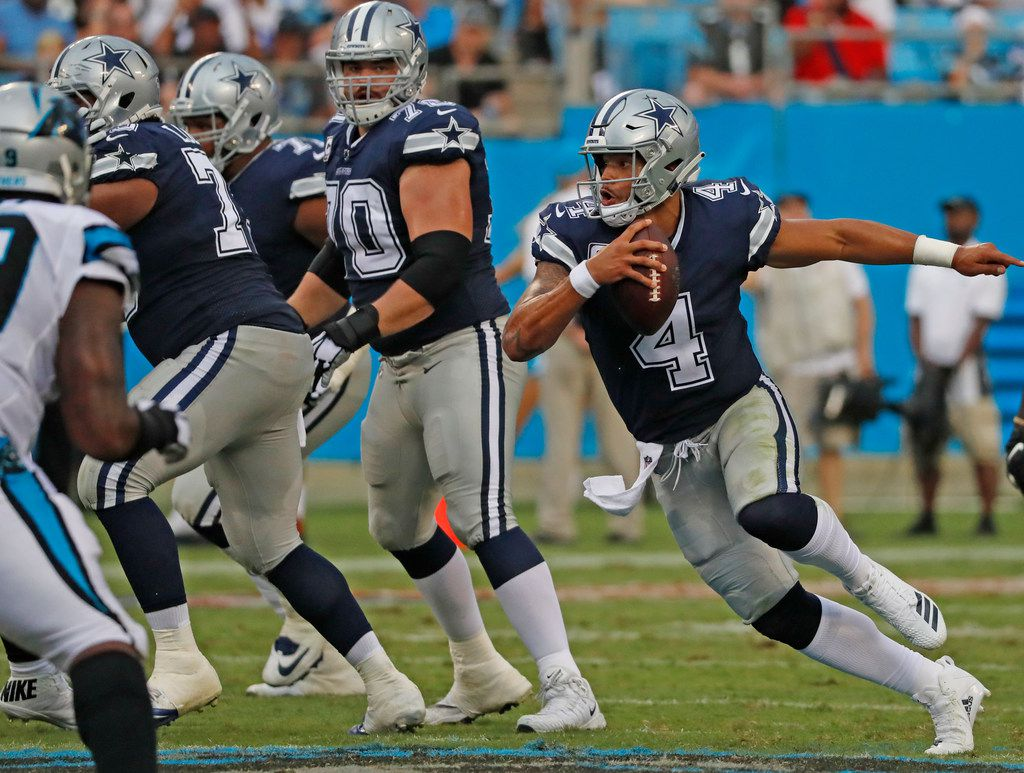 Dallas Cowboys offensive guard Zack Martin (70) watches as quarterback Dak Prescott (4) scrambles out of the pocket during the Dallas Cowboys vs. the Carolina Panthers NFL football game at Bank of America Stadium in Charlotte, North Carolina on Sunday, September 9, 2018. (Louis DeLuca/The Dallas Morning News)
