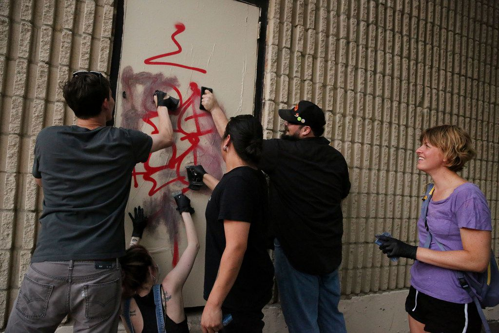 Adrienne Lichliter (right) watches as Jack Bryant (from left), Kristie Smyers, Angel Pacheco and Nathan Portnoy attempt to wipe graffiti off a door.